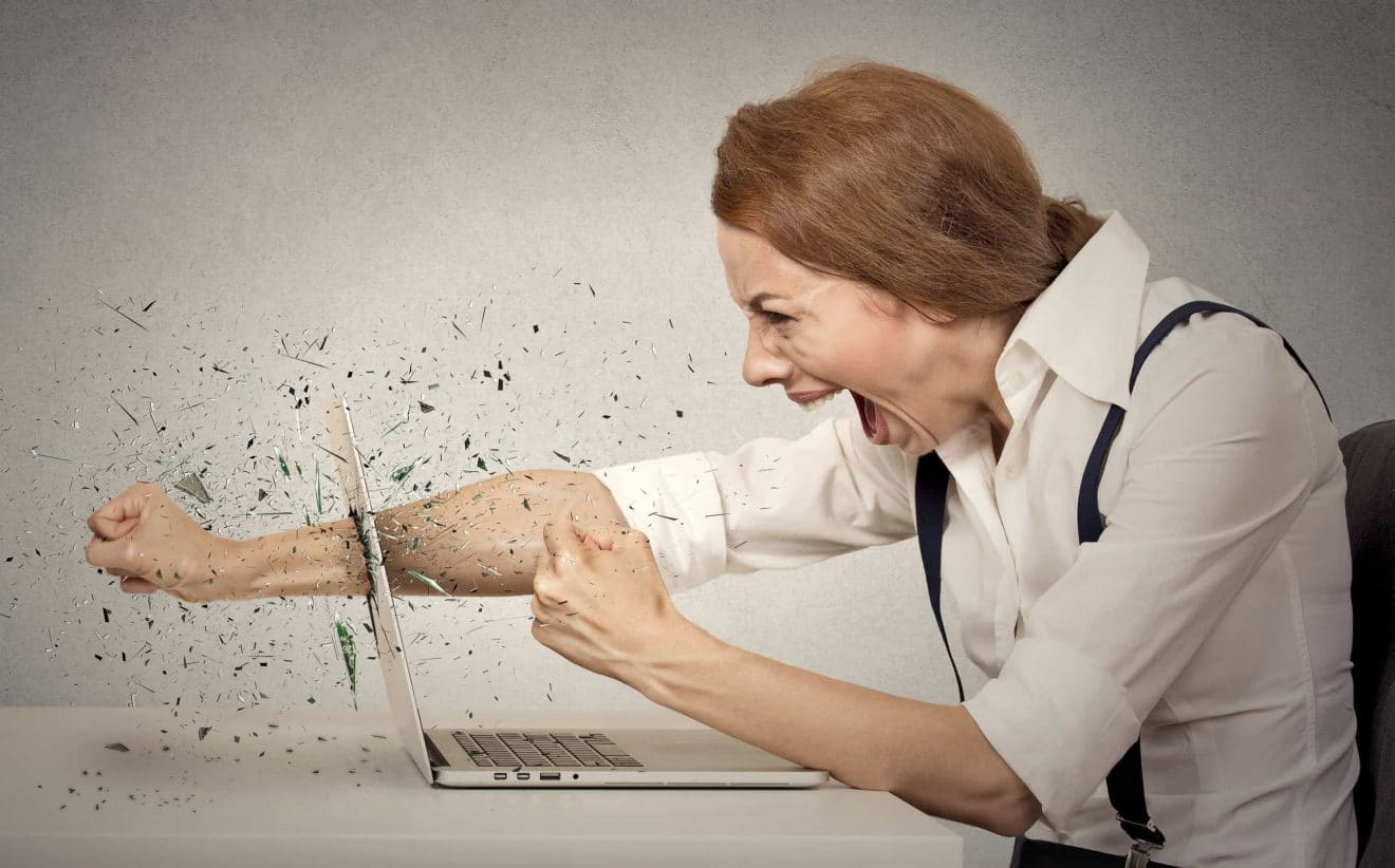 Furious businesswoman throws a punch into computer, screaming